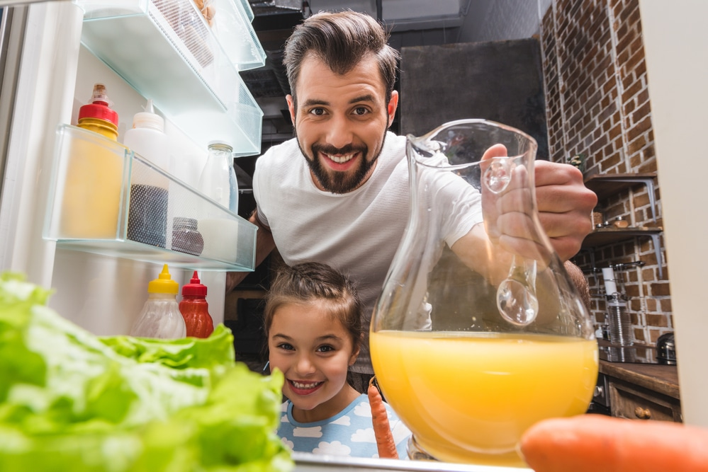 father and daughter taking orange juice from the fridge