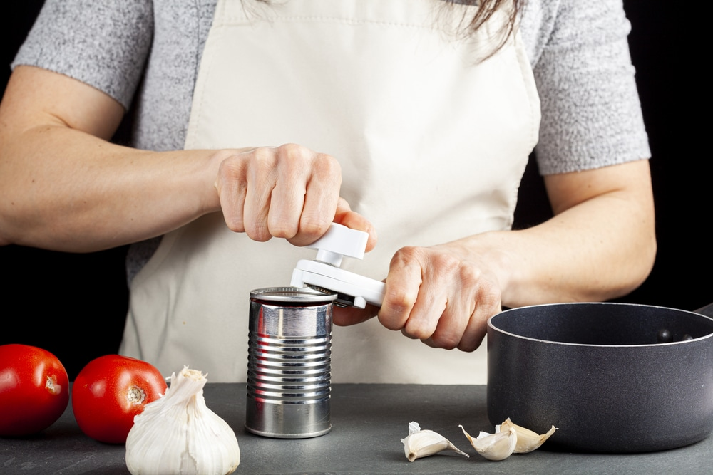 A woman carefully opening a canned tomato paste