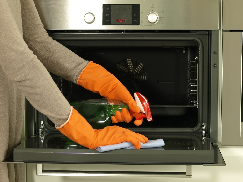 A woman cleans her kitchen equipment while wearing gloves.