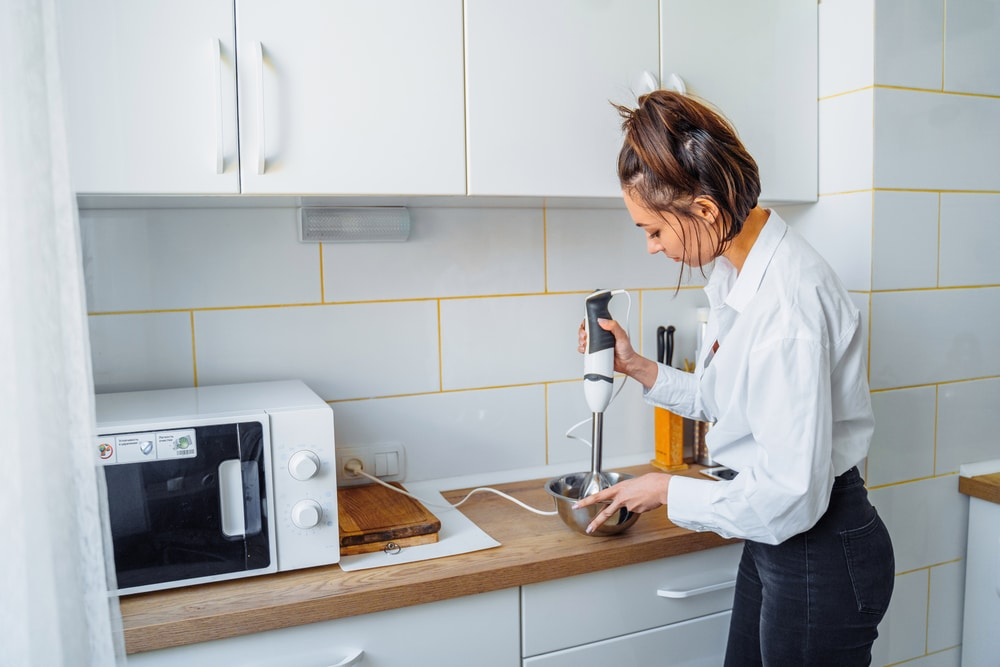 A woman prepares dough with an electric whisk