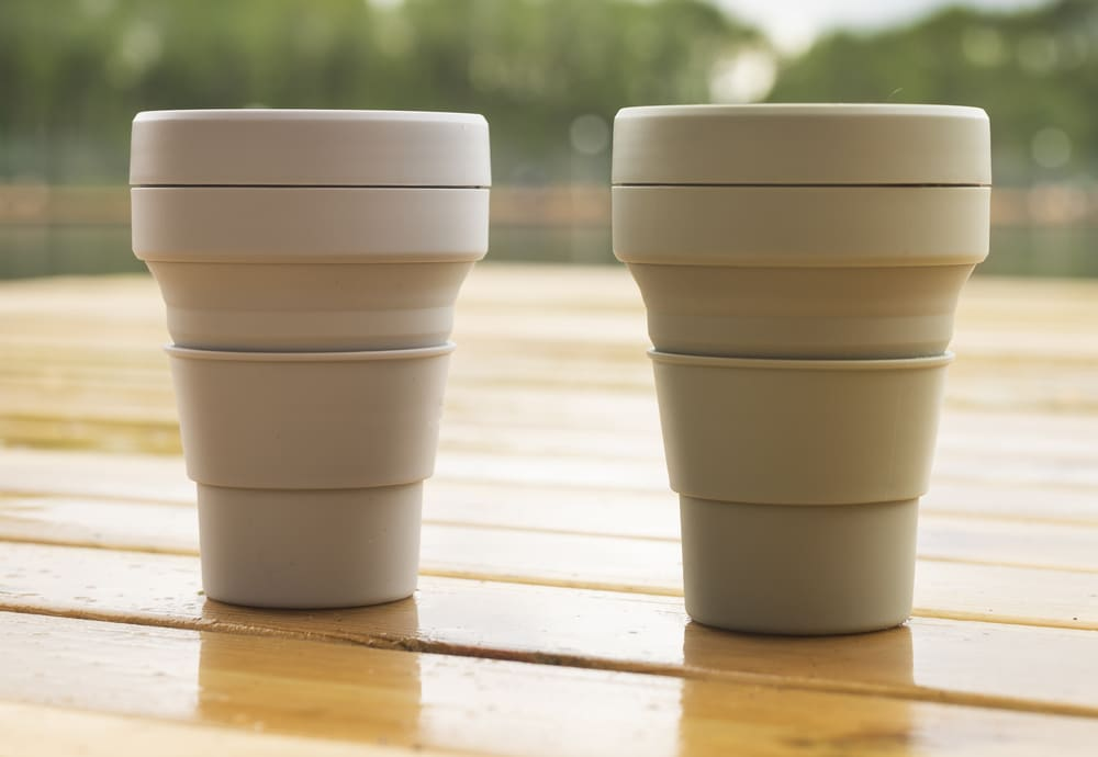 Two reusable silicon mugs on a wooden table